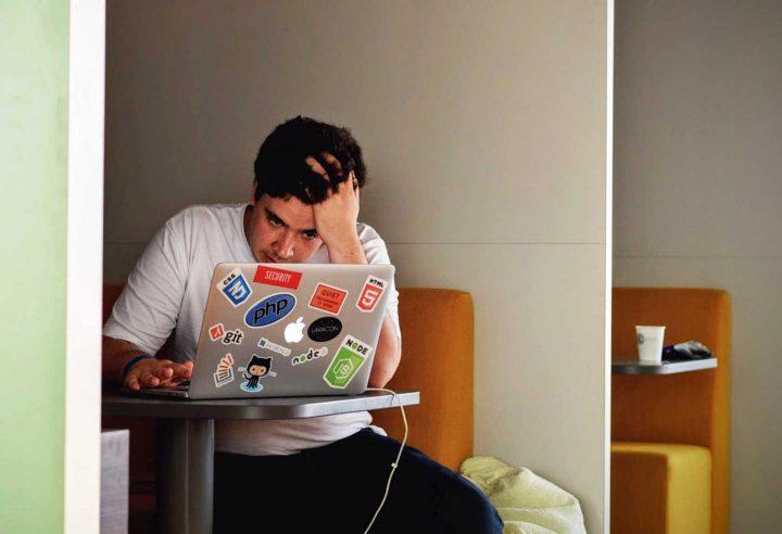 Um homem fracassado trabalhando no computador - Photo by Tim Gouw from Pexels